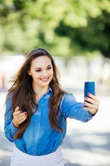 Closeup selfie-portret student van aantrekkelijk meisje in zonnebril met lang haar en sneeuwwitte glimlach in stad.