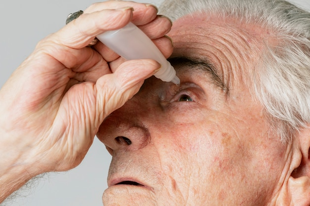Closeup senior man oogdruppels toe te passen