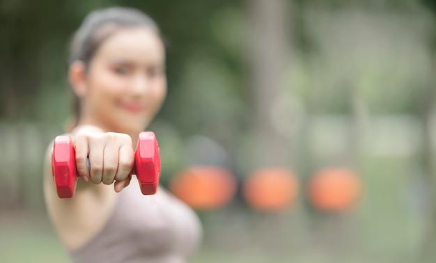 Closeup sportvrouw hand vooruit rode halter terwijl training in het park, kopieer ruimte.