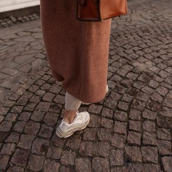 Closeup stijlvolle vrouwelijke benen in beige broek in modieuze lederen sneakers. mode meisje in lange jas in jeugdschoen loopt op stenen weg in de stad. nieuwe collectie damesschoenen. lente casual stijl.