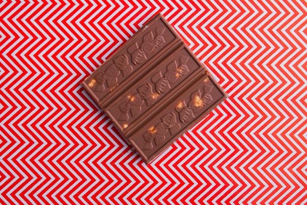 Closeup stuk bruine chocoladereep met rode en witte achtergrond and
