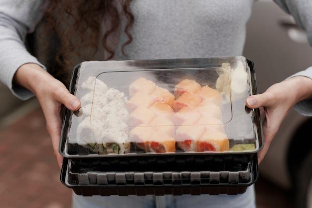 Closeup sushi in box gezonde voeding online service. meisje houdt 2 sushi-sets in handen. japanse keukenbroodjes, sojasaus, wasabi.