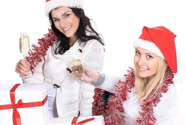 Closeup.three jonge vrouwen in hoeden van de kerstman met kerstcadeaus en glazen champagne. het concept van de viering.