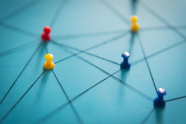 Closeup thumbtack netwerkverbindingen arrangement van kleurrijke pinnen gekoppeld aan elkaar met een string