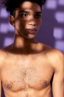 Closeup verticaal portret van jonge man poseren met schaduw op gezicht model transgender naakte torso