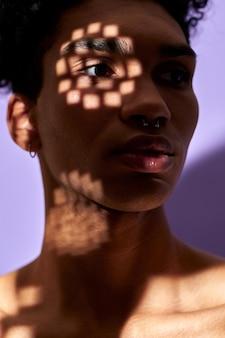 Closeup verticaal portret van latino jonge man gezicht in textuur schaduwen lichten op oog trans gender