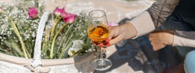 Closeup vrouw hand met een wijnglas met witte wijn. mand met bloemen op picknickdeken. horizontale banner of koptekst.