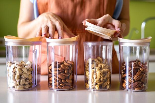 Closeup vrouw handen in schort plaatsen van verschillende noten in glazen pot opslagcontainer in de keuken