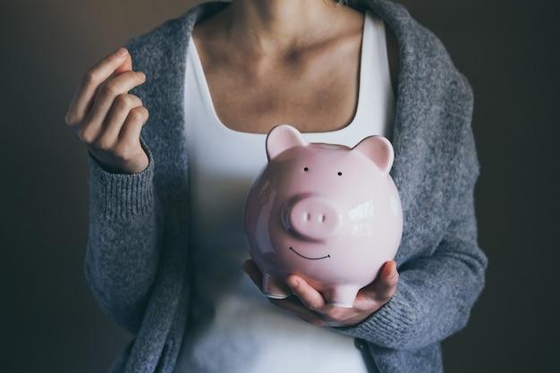 Closeup vrouw met gelukkig spaarvarken en geld gast hand vrouw bespaart geld huishoudelijke betalingen