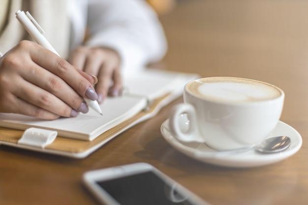 Closeup vrouwelijke handen maken aantekeningen op papier in kladblok gebruik pen tafel cafetaria schrijven dagboek planning