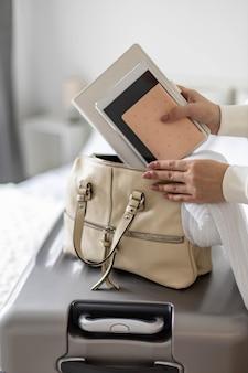 Closeup vrouwelijke handen zetten documenten tablet pc kladblok dagboek in handtas klaar om vakantie te reizen