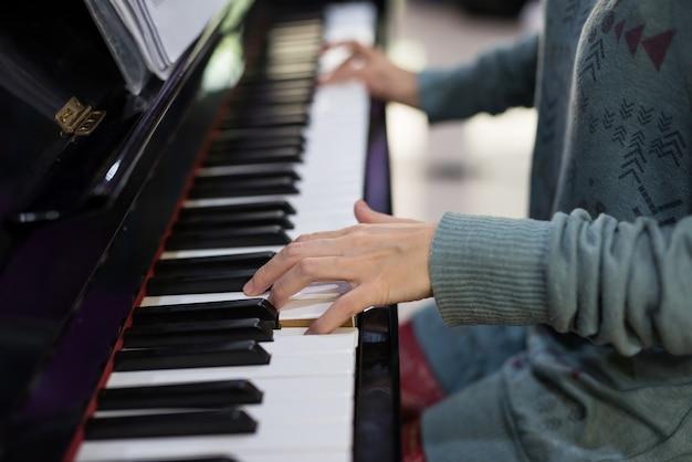 Closeup vrouwelijke pianist handen spelen op klassiek pianotoetsenbord. muziek instrumenten. vrije tijd en hoppig in huis concept. muziek spelen voor familie.