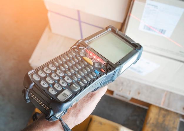 Closeup werknemer met barcode scanner scant op pakketdozen