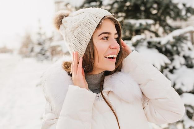 Closeup winter portret jonge mooie vrouw in witte gebreide muts uitdrukken naar kant op straat vol met sneeuw.