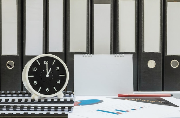 Closeup witte klok voor versieren in 1 uur bureau van officier met werk papier