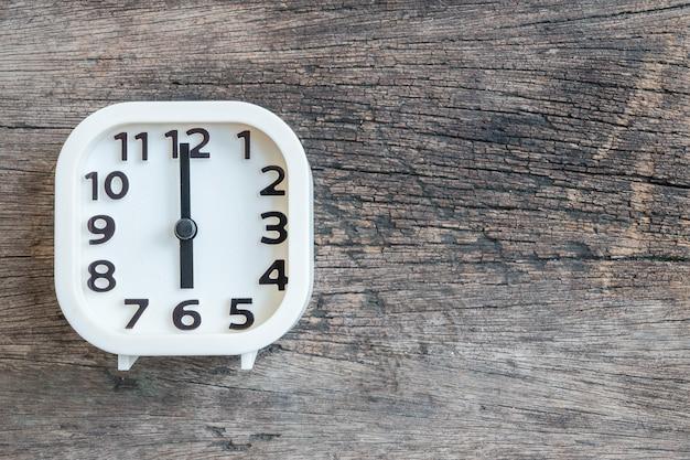 Closeup witte klok voor versieren in 6 uur op oude houten vloer gestructureerde achtergrond met kopie ruimte