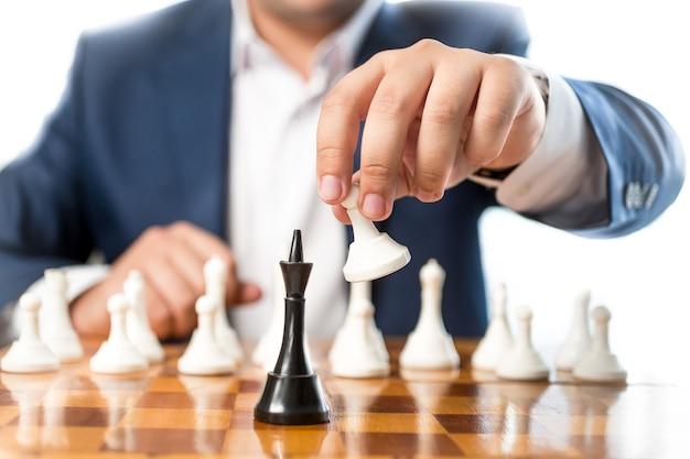 Closeup zakenman schaken en het verslaan van zwarte koning black