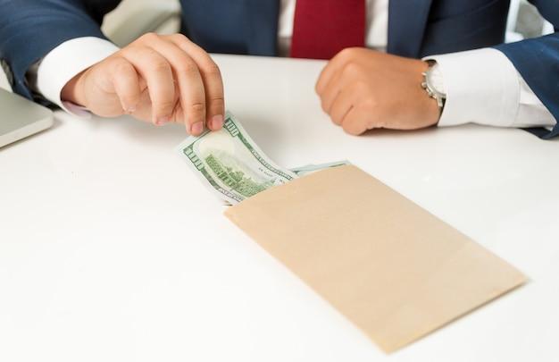 Closeup zakenman trekken bankbiljet uit envelop liggend op tafel