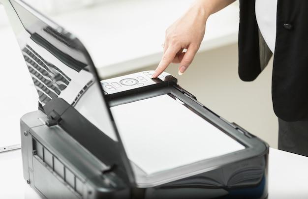Closeup zakenvrouw knop op kopieermachine op kantoor te drukken