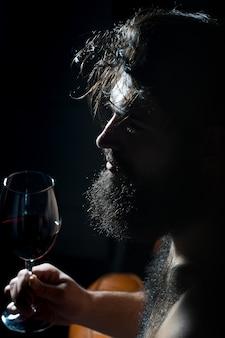Closeup zijaanzicht van een knappe trieste peinzende jonge volwassen man met lange zwarte weelderige mooie baard en snor met glas met rode wijn binnen op onscherpe achtergrond, verticale afbeelding
