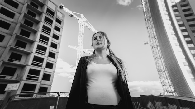 Closeup zwart-wit portret van gefrustreerde en depressieve vrouw poseren tegen wolkenkrabbers in aanbouw