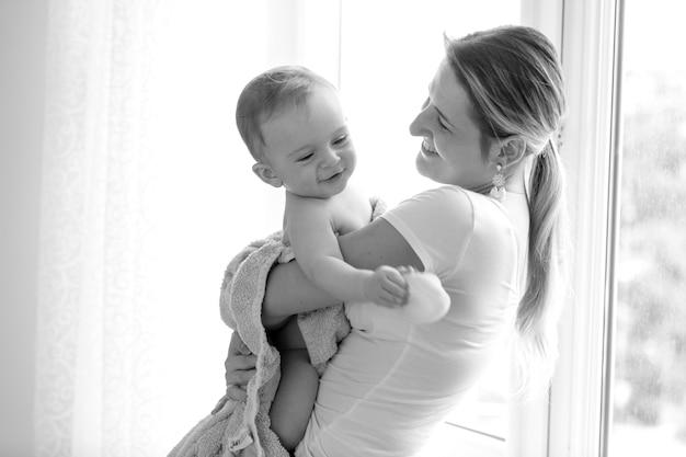 Closeup zwart-wit portret van gelukkig lachende moeder die haar baby vasthoudt na het baden