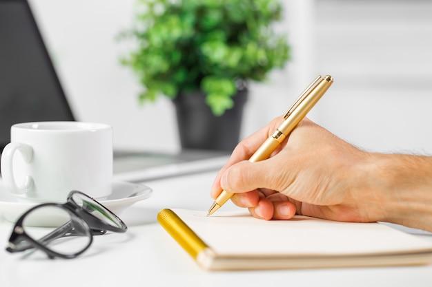 Closewithup van mannelijke zakenmanhand die nota's in bureau maken