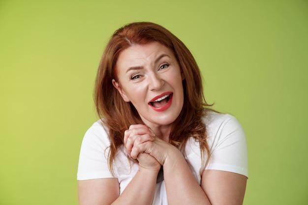 Closeyp aangeraakt teder vriendelijk roodharige oma van middelbare leeftijd zuchtende blik bewondering verrukking gesp handen hartverwarmend mooi tafereel glimlachen kantelend hoofd onder de indruk tevreden stand groene muur