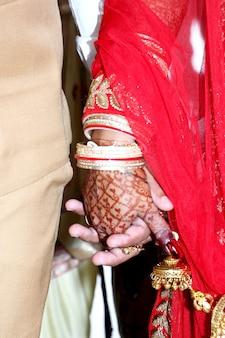 Closup van indiase jonge volwassen mannelijke bruidegom en vrouwelijke bruid hand in hand