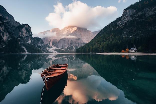 Clouds staat bovenaan. houten boot op het kristalmeer met majestueuze erachter berg. reflectie in het water. kapel ligt aan de rechter kust