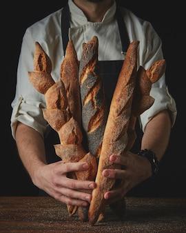 Clous omhoog handen man met stokbrood op een houten tafel