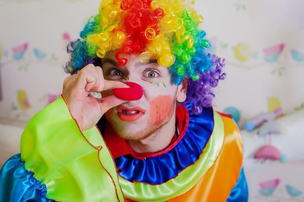 Clown duwt zichzelf op de neus.