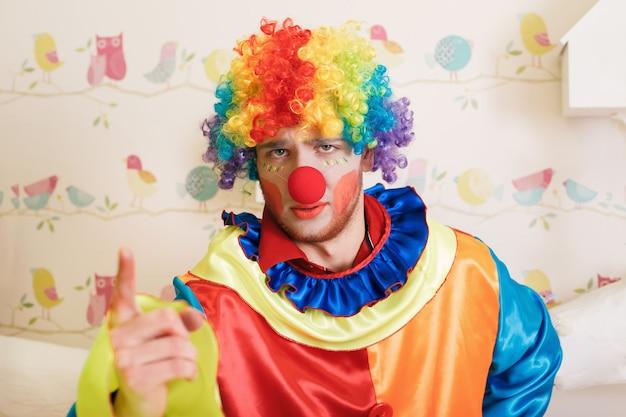 Clown in grappig kostuum toont vinger.