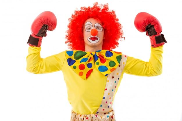 Clown in rode pruik en bokshandschoenen die spieren tonen.