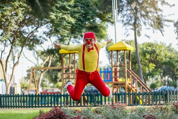 Clown lacht tijdens het springen in een park rode broek geel shirt