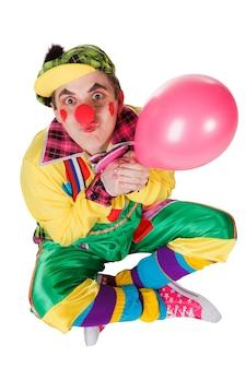 Clown met een ballon in een hand op de witte achtergrond wordt geïsoleerd die