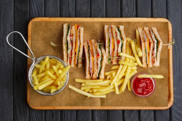 Club-sandwich met frieten in metaalmand