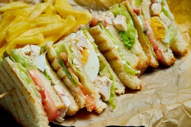 Club sandwich met ham, tomaten, gepekelde komkommer, ei, kaas en sla op een houten dienblad. detailopname. lekker fastfood.
