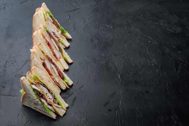 Club sandwich met vlees, kaas, tomaat, ham, op zwarte achtergrond met kopie ruimte voor tekst