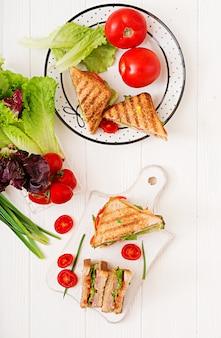 Club sandwich - panini met ham, kaas, tomaat en kruiden. bovenaanzicht