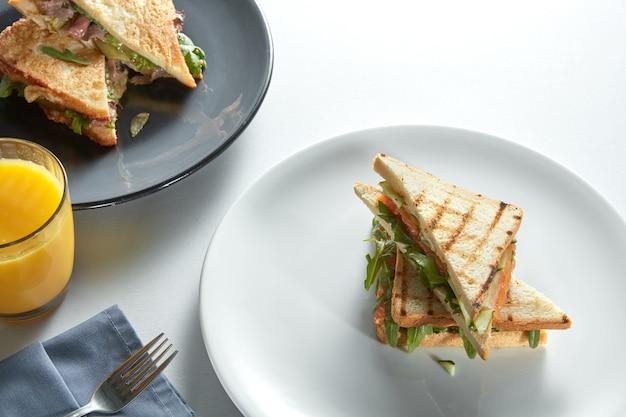 Club sandwich twee met verschillende vullingen en jus d'orange op tafel