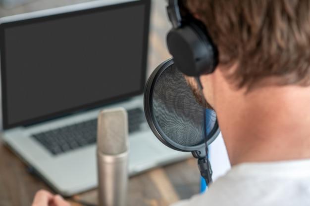 Clubhuis conferentie. een foto van een man met een zwarte koptelefoon die in de microfoon spreekt