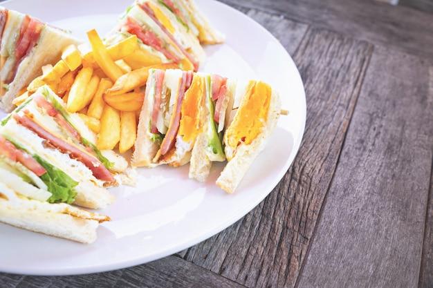 Clubsandwich met baconkaas en hamgroente en saus in witte plaat op lijst.