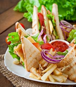 Clubsandwich met kaas, komkommer, tomaat, gerookt vlees en salami. geserveerd met frietjes.