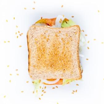 Clubsandwich op wit met tomaten, uien, sesam en salade wordt geïsoleerd die.