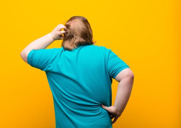 Clueless en verward voelen, een oplossing denken, met hand op heup en andere op hoofd, achteraanzicht