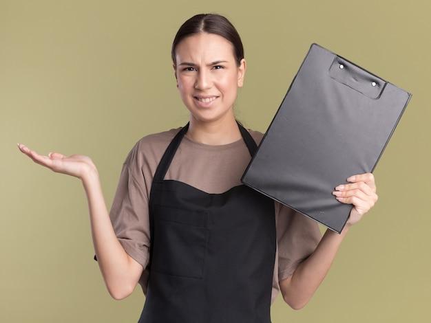 Clueless jong brunette kappersmeisje in uniform houdt hand open en houdt klembord geïsoleerd op olijfgroene muur met kopieerruimte
