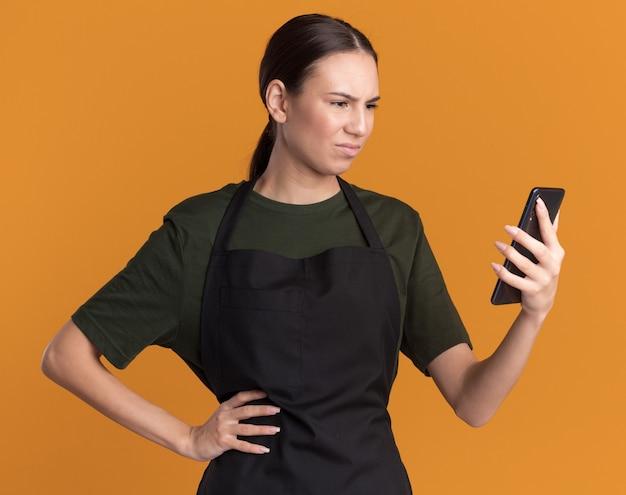 Clueless jong brunette kappersmeisje in uniform houdt vast en kijkt naar tondeuses