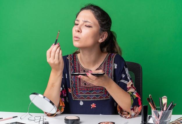Clueless jong brunette meisje zit aan tafel met make-uptools met oogschaduwpalet en kijkend naar make-upborstel