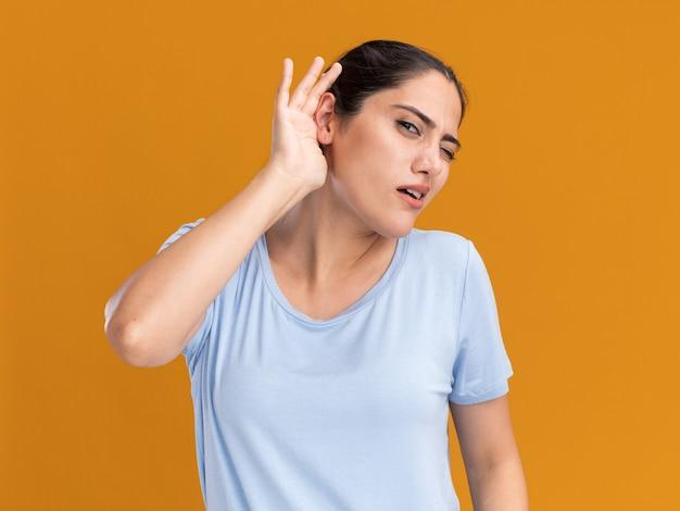 Clueless jong donkerbruin kaukasisch meisje houdt hand achter oor op sinaasappel